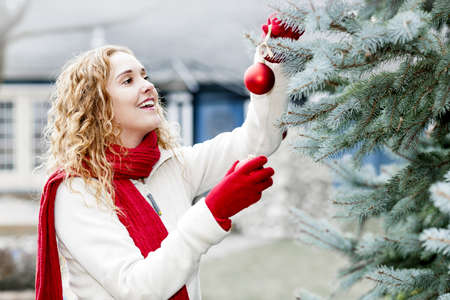 Portrait of smiling woman hanging Christmas ornaments on spruce tree outdoors in yard near home Stock Photo - 18341756
