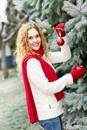 Joyful woman hanging Christmas ornaments on spruce tree outdoors in yard near home Stock Photo - 18341802