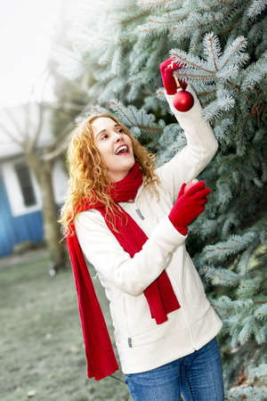 Joyful woman hanging Christmas ornaments on spruce tree outdoors in yard near home Stock Photo - 18341786