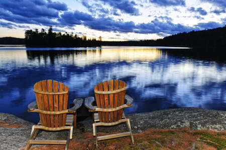 adirondack chair: Landscape with adirondack chairs on shore of relaxing lake at sunset in Algonquin Park, Canada