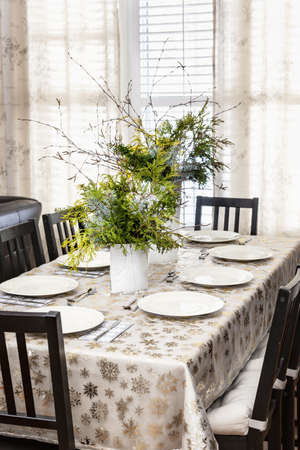 gold table cloth: Dining table decorated for Christmas with eight place settings and evergreen centerpiece Stock Photo
