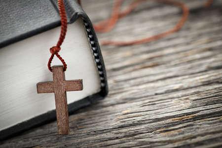 Close-up van houten christelijke kruis ketting naast de heilige Bijbel Stockfoto