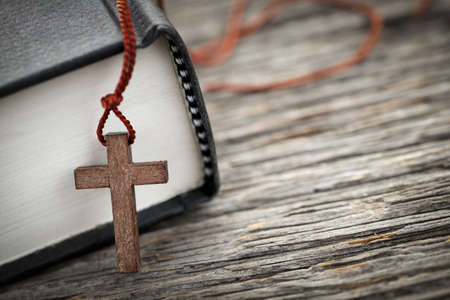 prayer: Closeup of wooden Christian cross necklace next to holy Bible