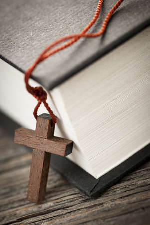 Closeup of wooden Christian cross necklace next to holy Bible photo