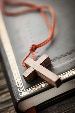 Closeup of simple wooden Christian cross necklace on holy Bible Stock Photo - 18654232