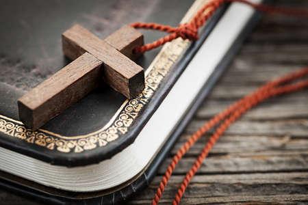 Close-up van eenvoudige houten christelijke kruis ketting op heilige Bijbel