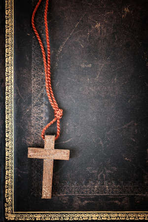 Closeup of simple wooden Christian cross necklace on holy Bible with copy space photo