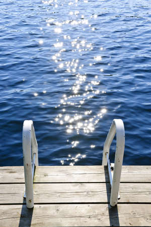 Dock and ladder on calm summer lake with sparkling water in Ontario Canada Stock Photo - 18654228