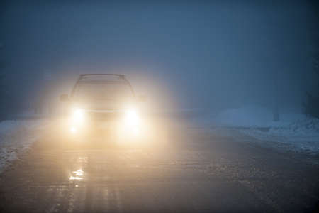 Bright headlights of a car driving on foggy winter road photo