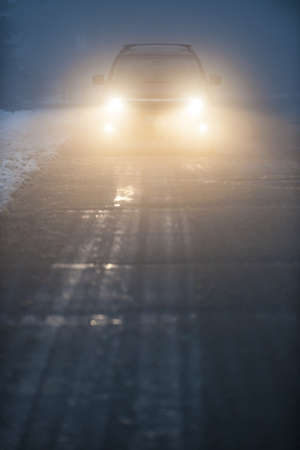 headlights: Bright headlights of a car driving on foggy winter road Stock Photo