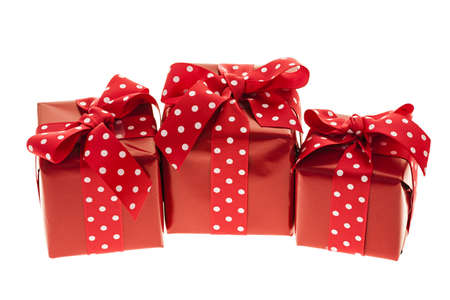 three gift boxes: Three presents wrapped in red paper with polkadot ribbon