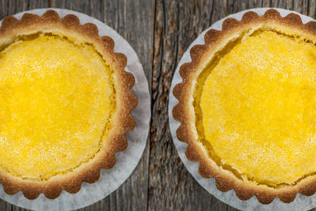 Two fresh gourmet lemon dessert tarts on wood background from above Stock Photo - 18654238
