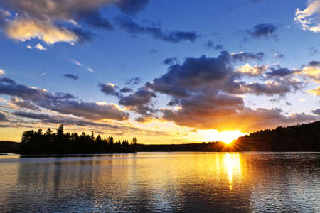 Sun setting over tranquil lake and forest in Algonquin Park, Canada Stock Photo - 18654235