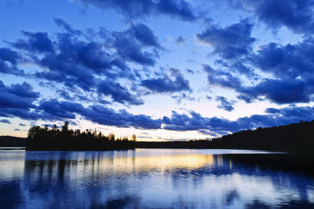 provincial forest parks: Sun setting over tranquil lake and forest in Algonquin Park, Canada Stock Photo
