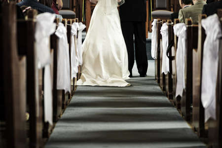 christian marriage: Bride and groom getting married in church view from aisle