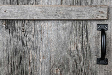 Distressed rustic barn wood door with handle as textured background photo