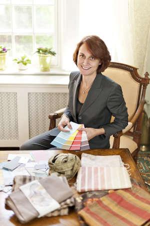 Female interior designer with color samples sitting at desk Stock Photo - 18971724