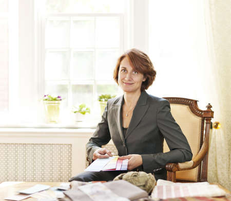 designer: Female interior designer with color samples sitting at desk Stock Photo