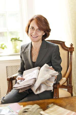 designer: Female interior designer with fabric samples sitting at desk