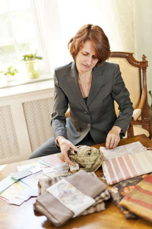 designer: Female interior designer choosing from fabric samples sitting at desk Stock Photo