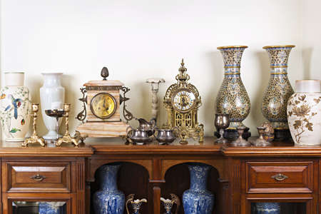 antique vase: Various antique clocks vases and candlesticks on display Stock Photo