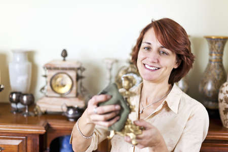 Happy caucasian woman proudly polishing antique collection Stock Photo - 18971725