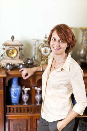 Happy proud woman standing next to her collection of antiques Stock Photo - 18971723