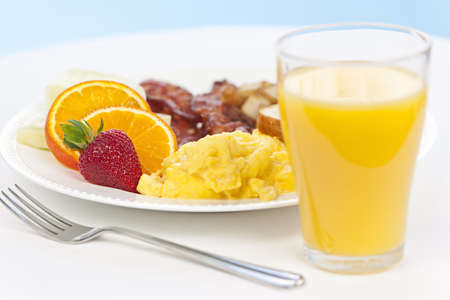 Healthy breakfast of scrambled eggs bacon fruit and orange juice photo