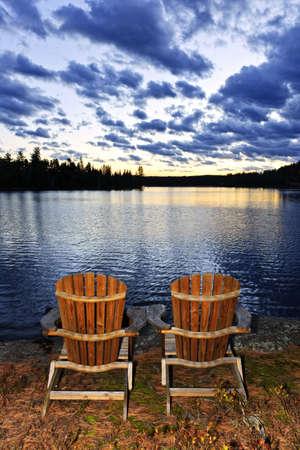 カナダのアルゴンキン州立公園で日没時穏かな湖の岸に adirondack の椅子のある風景します。