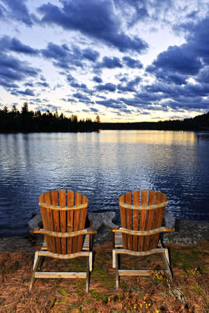 Landscape with adirondack chairs on shore of relaxing lake at sunset in Algonquin Park, Canada photo