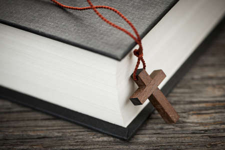 Closeup of wooden Christian cross necklace next to holy Bible Stock Photo - 19014577