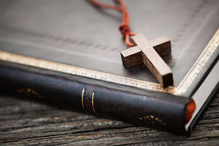 Closeup of simple wooden Christian cross necklace on holy Bible Stock Photo - 19014579