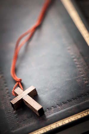 christian faith: Closeup of simple wooden Christian cross necklace on holy Bible with copy space Stock Photo