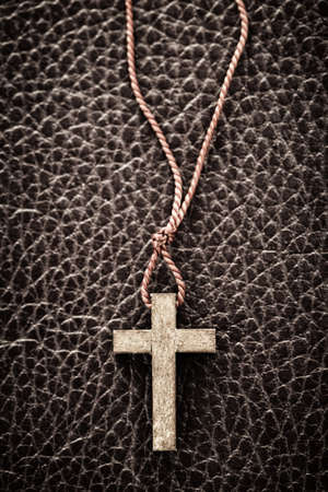 Closeup of simple wooden Christian cross necklace on leather bound holy Bible photo