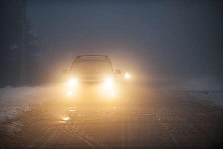 明るい車のヘッドライトの霧、冬の道路上で運転