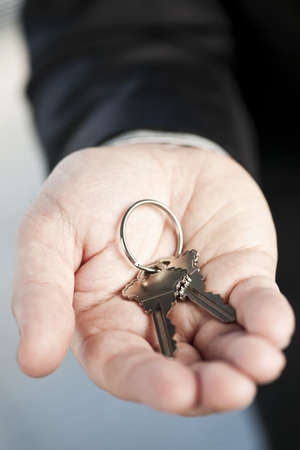 Male hand offering two new house keys on key ring Stock Photo - 18971728