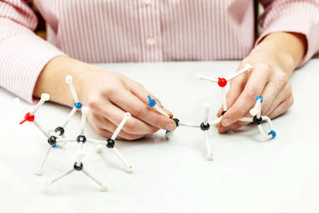 Hand of female student assembling amino acid molecule models for science project Stock Photo - 18971726