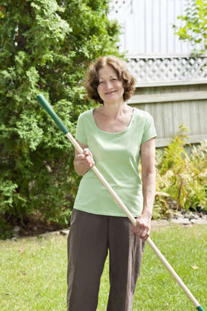 Senior woman smiling holding rake and gardening outside Stock Photo - 19341221