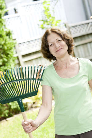 Senior woman smiling holding rake for yard work outside photo