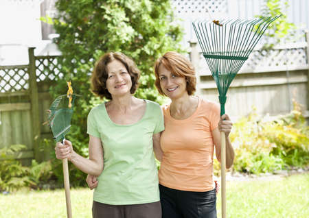 Mother and daughter holding rakes gardening doing yard work outside photo