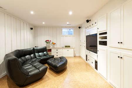 corcho: Terminado el sótano de la casa residencial con centro de entretenimiento, sofá y televisión de pantalla plana.