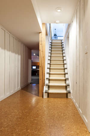 Stairway to finished basement in home interior with wood paneling and cork flooring photo