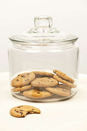 Glass cookie jar with chocolate chip cookies Stock Photo - 19382512