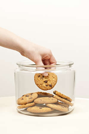 Hand taking chocolate chip cookie from glass jar