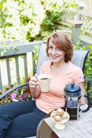 Happy woman relaxing with coffee and cookies on deck chair in backyard at home Stock Photo - 19535952