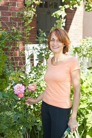 garden shears: Feliz mujer de mediana edad de jardiner�a y poda rosal con tijeras de jard�n