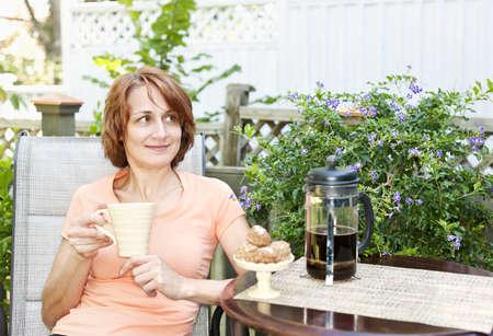 Gelukkige vrouw ontspannen met koffie en koekjes op een ligstoel in de achtertuin thuis