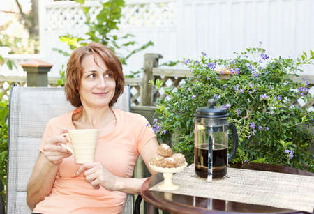Happy woman relaxing with coffee and cookies on deck chair in backyard at home Reklamní fotografie