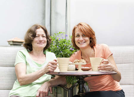 Mature women relaxing with coffee and cookies outside on patio Stock Photo - 19535945
