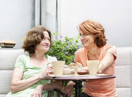 amigas conversando: Las mujeres maduras relajarse y hablar con café en el patio en el patio trasero en su casa Foto de archivo
